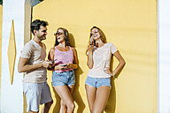 Three happy friends with cell phones outdoors - KIJF01608
