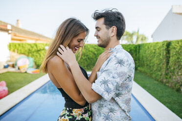 Affectionate happy couple at the poolside - KIJF01614