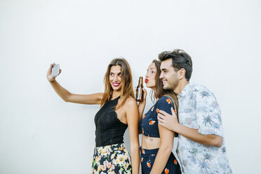 Friends taking a selfie with smartphone in front of white wall - KIJF01620