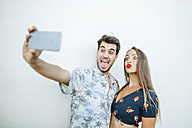 Playful couple taking a selfie with smartphone in front of white wall - KIJF01626