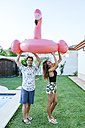 Couple holding pink flamingo float at the poolside - KIJF01629