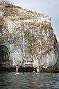 Mexico, Banderas Bay, Los Arcos National Marine Park, man and woman paddleboarding, exploring caves and rock formations at sea - ABAF02167