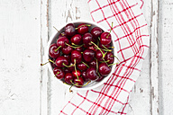 Bowl of cherries and kitchen towel on white wood - LVF06158