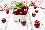 Cardboard box of cherries, leaves and kitchen towel on white wood - LVF06161