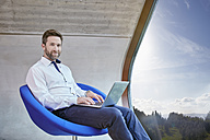 Businessman sitting on chair in attic office using laptop - RHF01923
