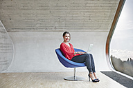 Portrait of smiling woman sitting on chair in attic office with laptop - RHF01995