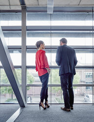 Businessman and businesswoman talking at the window - RHF02004