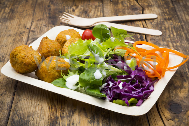 Falafel and salad on wooden disposable plates and cutlery - LVF06164