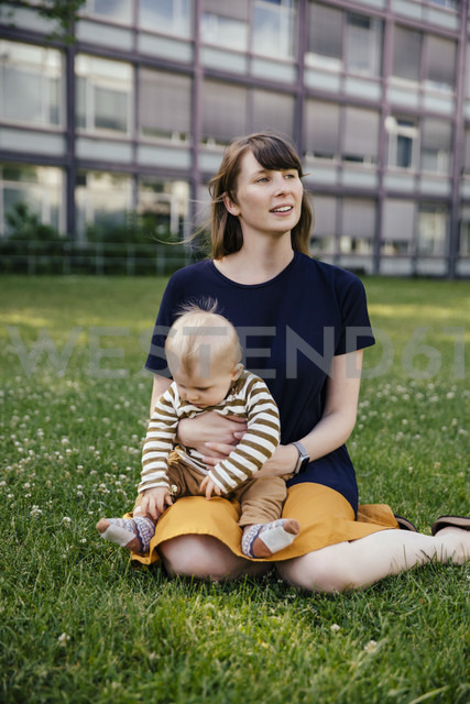 Mother sitting with her baby boy on a meadow - MFF03650