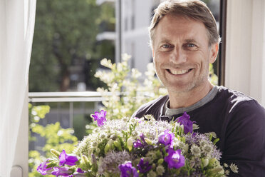 Portrait of smiling man with bunch of flowers - MFF03656