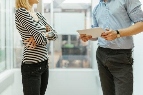 Businessman and woman standing in corridor, talking - ZEDF00616
