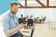Businessman in office meeting using smartphone - ZEDF00640