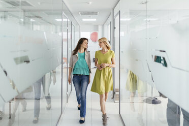 Two female colleagues walking in office corridor - ZEDF00643