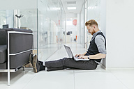 Businessman in office sitting on floor, using laptop - ZEDF00652