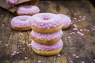 Stack of Doughnuts with pink icing and sugar granules on wood - LVF06173