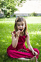 Portrait of little girl wearing red summer dress sitting on a meadow eating cherries - LVF06181