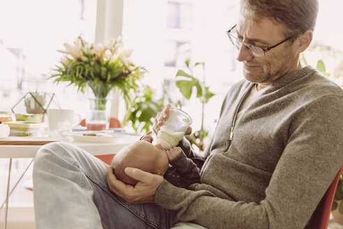 Father bottle-feeding his newborn baby boy at home - MFF03660