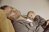 Father taking a nap with newborn awake on his chest - MFF03663