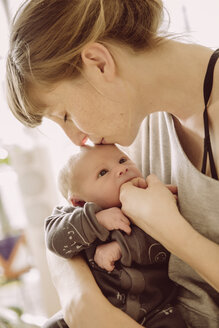 Mother testing newborn baby's hunger with her finger and kissing its forehead - MFF03669