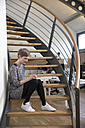 Woman sitting on stairs in modern office looking at cell phone - FKF02340