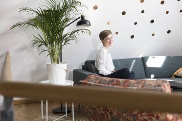 Woman using laptop on couch in modern office - FKF02343