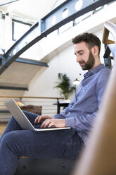 Man sitting on floor using laptop in modern office - FKF02358