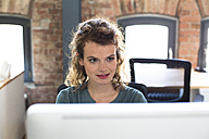 Young woman working at desk in modern office - FKF02376
