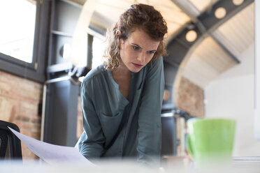 Young woman working at desk in modern office - FKF02385
