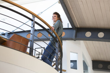 Smiling woman leaning against railing in modern office - FKF02388