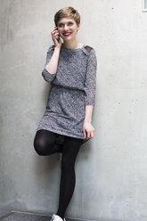 Smiling woman on cell phone at concrete wall - FKF02397