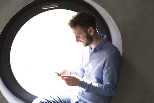 Smiling man sitting in round window looking at cell phone - FKF02400
