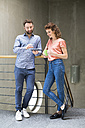 Man and woman in staircase with cell phone and cup of coffee - FKF02406