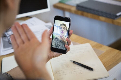 Close-up of woman at desk taking a selfie - FKF02412
