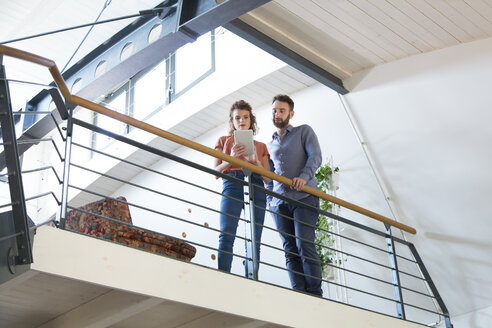 Colleagues standing on upper floor sharing tablet - FKF02415