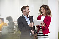 Businessman and businesswoman with tablet talking in office - ZEF13996