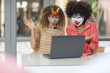 Two women in office wearing masks sharing laptop - ZEF14011