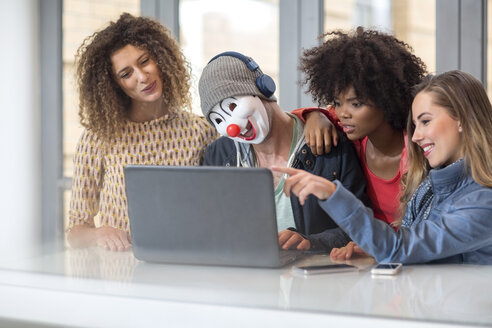 Man in office wearing mask sharing laptop with colleagues - ZEF14014