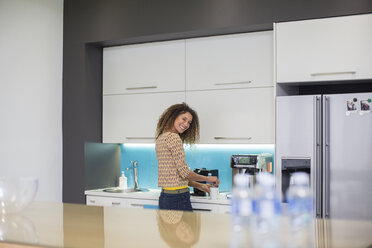 Smiling woman in office kitchen making a beverage - ZEF14017
