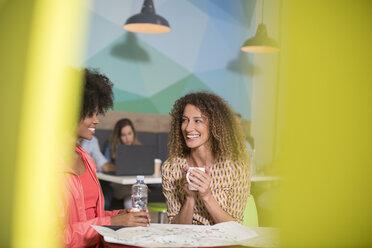 Two women talking in office lounge - ZEF14023