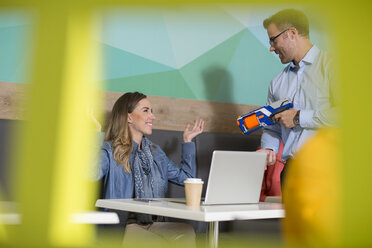 Colleagues having fun in office break area with toy gun - ZEF14026