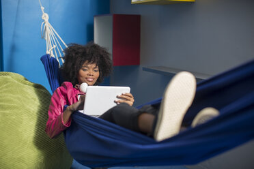 Employee with tablet relaxing in hammock - ZEF14032