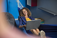 Happy employee with laptop relaxing in hammock - ZEF14035