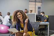 Smiling woman with tablet sitting in office - ZEF14041