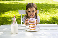Happy girl with stack of donuts on garden table - LVF06191