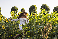 Happy woman in a sunflower field - MAUF01077