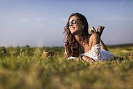 Happy woman lying in a field - MAUF01080