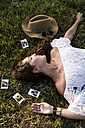 Happy woman lying in a field surrounded by instant photos - MAUF01086