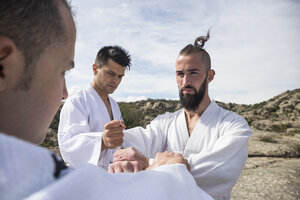 Men doing grip exercises during a martial arts training - ABZF02107