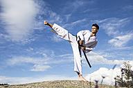 Man with a katana sword doing a high kick - ABZF02125
