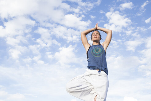 Woman doing a yoga exercise under sky with clouds - ABZF02128